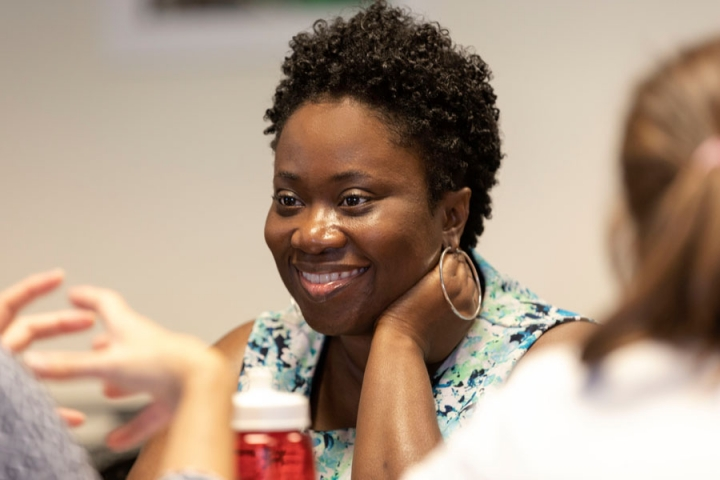 Close-up of faculty member smiling while engaged in a discussion