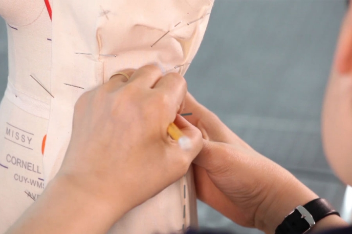 Close-up of hands draping fabric on a dress making form