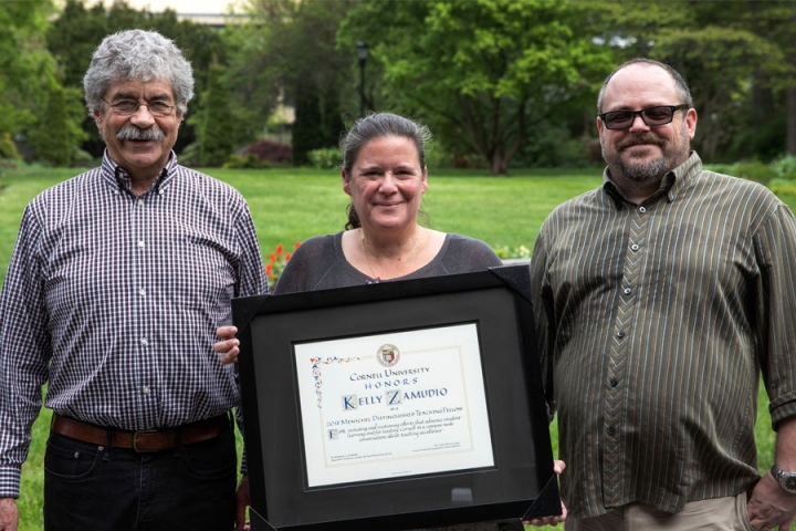 Kelly Zamudio holding her Menschel Distinguished Teaching Fellow Award standing between two former fellows